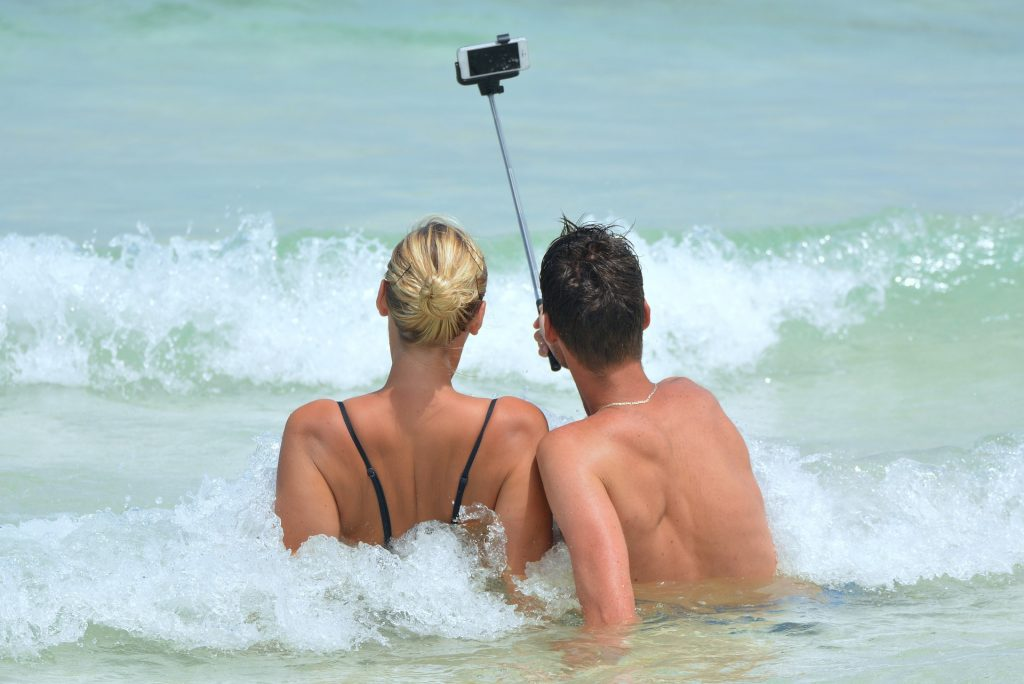Man & woman in the sea taking a selfie using a selfie stick